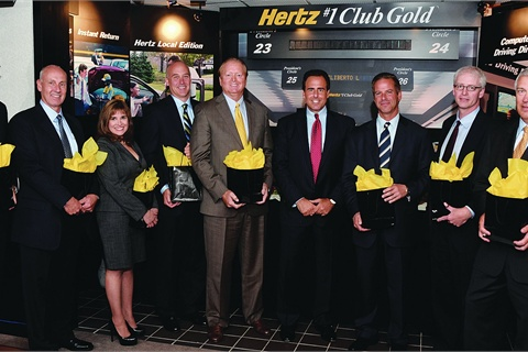 Overseen by Hertz CEO Mark Frissora (center, wearing a red tie) is Donlen's senior management team (l-r, holding bags): Tom Callahan, Dave Lodding, Carla Garfinkle, Dennis Straight, Michael Lewis, Gary Rappeport, Michael Manfred, and Barry Steel attended the ceremony held at Hertz's Global Headquarters in Park Ridge, N.J., marking the sale agreement of Donlen to Hertz Global Holdings.