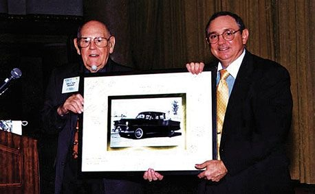 John Sohl (left), founder of Auto Driveaway, and son BrandonSohl, past president of Auto Driveaway, display a picture of the first car John Sohl ever shipped, a 1952 Ford. The photo was presented to John Sohl at the company's 50th anniversary celebration in 2002.