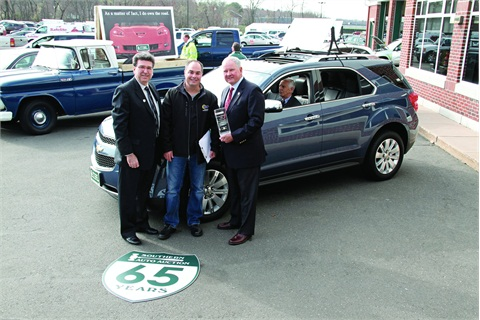 (L–R) Dan Kennedy, manager for GM Remarketing; Todd Caputo, owner of Sun Chevrolet, Inc.; and Larry Tribble, Southern Auto Auction owner and president, pose in front of the 14 millionth remarketed GM vehicle, a 2011 blue Chevrolet Equinox, which Caputo purchased during a sale on March 28.
