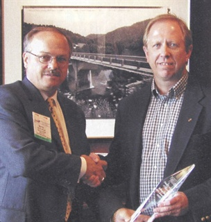 Jeffrey Smith (right), director of distribution for PPG AutoGlass, received Fleet Financials' 2003 Fleet Executive Award. Wayne Smolda (left), CEO of the CEI Group, congratulates the winner.