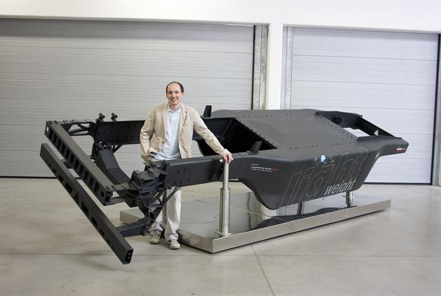 Gregor Schwarz of Austria's Engineering Center Steyr stands proudly with the lightweight monocoque truck frame he designed.