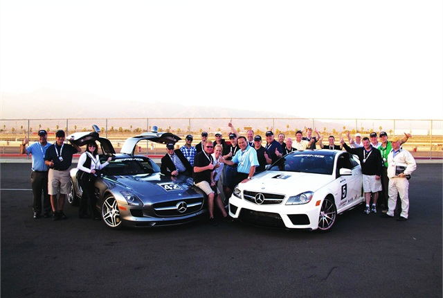 Gathered around an SLS AMG (left) and CL63 AMG, fleet professionals give a thumbs up after completing a one-day AMG Driving Academy at the Auto Club Speedway in Fontana, Calif.