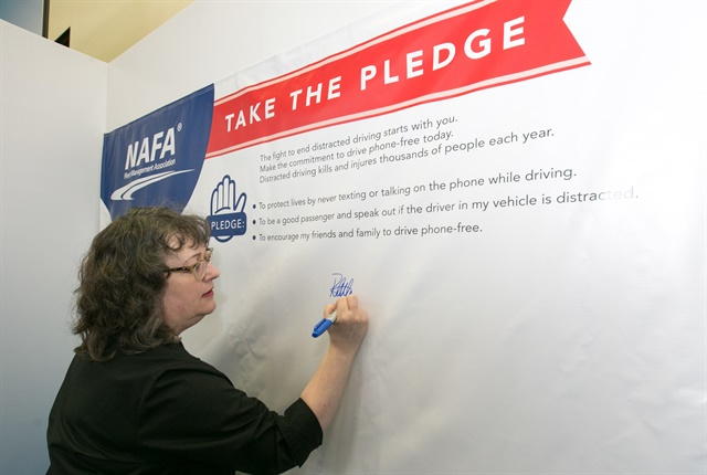 Photo of NAFA president, Ruth Alfson, signing the NAFA pledge to end distracted driving at the conference courtesy of NAFA Fleet Management association.