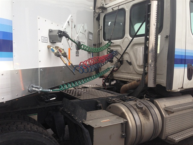 """Lower green cord is the """"stinger"""" that carries power and a return ground line to trailer batteries that operate the liftgate. Connector cord should remain plugged in to keep a load on the line while its circuit is tested. Photo: Con-Way Freight"""