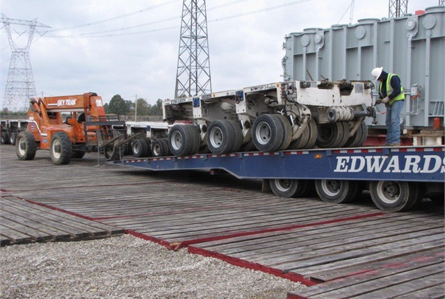 Crewmen assemble the transporter from modules, each with three axle-lines and 24 wheels, carried to a Lewis Center substation and rail siding. Transformer waits on railcar in the background.