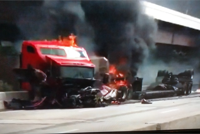 <p><strong>Tractor's frame is twisted and its hood gone as flames engulfs its rear. But the cab appears intact and motorists were able to pull out the driver and his dog.  </strong></p>