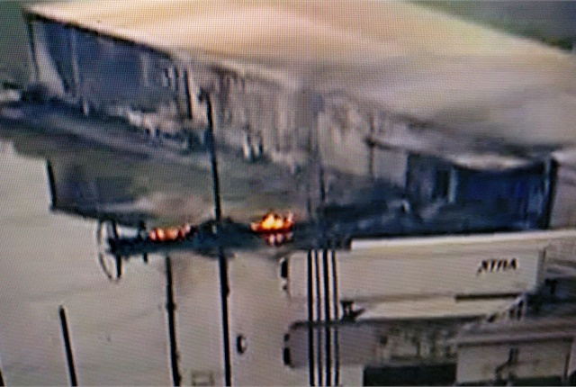 "<p><strong>Aerial video shows what appear to be remains of a smouldering trailer. After contaminated fuel shut down its reefer unit, a temperature-sensitive chemical stored inside ""combusted."" Another reefer van is parked nearby. <em>Image: Screen capture, Fox News</em></strong></p>"