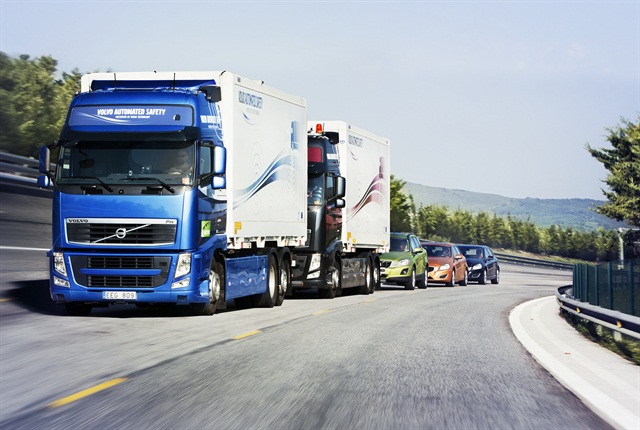 """In the Sartre project, three self-driving Volvo cars """"platoon"""" behind a commercial truck."""
