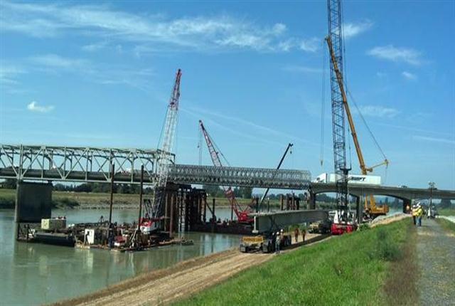 A 162-foot-long, 168,000-pound concrete beam has arrived at the job site aboard a 14-axle rig. I-5 bridge over the Skagit River is being rebuilt after a section was knocked down by an oversize load aboard a semi. Photos by Washington state Department of Transportation.