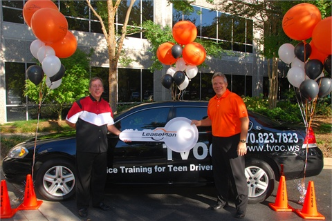 Michael Pitcher (right), president and CEO of LeasePlan USA, presents Woodrow Gaines (left), president of FEAR THIS, Inc., with the keys to a 2008 Chevrolet Impala.