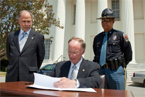 Alabama Gov. Robert Bentley signs into law a measure that prohibits texting while driving. State Representative Jim McClendon (left) and Public Safety Director Col. Hugh McCall (right) look on.