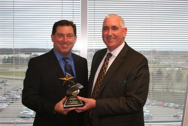 Bob Brown Jr., great lakes sales manager for Automotive Fleet (left), presented the Fleet Car of the Year award to John Ruppert, general manager, commercial and government operations at Ford Motor Company.