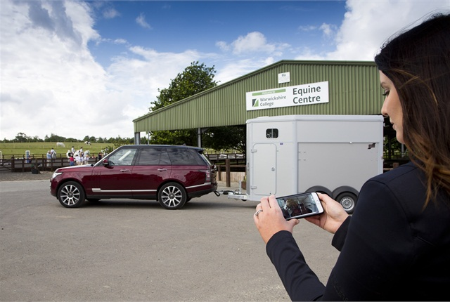 A woman demonstrates Cargo Sense, a smartphone app that lets drivers remotely monitor trailer cargo. Photo courtesy of Land Rover.