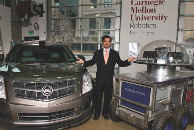 Professor Raj Rajkumar poses between CMU's latest self-driving car, a Cadillar SRX, and the university's first autonomous vehicle 30 years ago. Photo courtesy of Carnegie Mellon University in Pittsburgh.