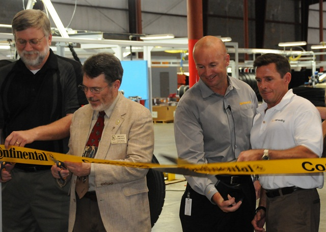 <p>Scott Snyder, right, with Paul Williams of Continental and local dignitaries prepare to cut the ribbon officially opening DLS Retreading in Fort Mill S.C.</p>