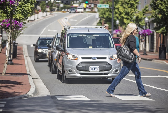 <p>A pedestrian crosses the street in front of what appears to be a driverless van -- but isn't. <em>Photo courtesy of Ford.</em></p>