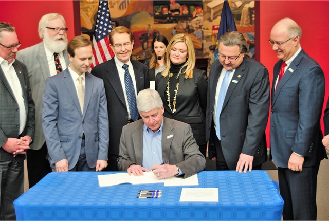 Michigan Gov. Rick Snyder on Dec. 9 signs autonomous vehicle legislation during a special ceremony at the Automotive Hall of Fame Museum, surrounded by state legislators and auto industry leaders. Photo courtesy of the governor's office.