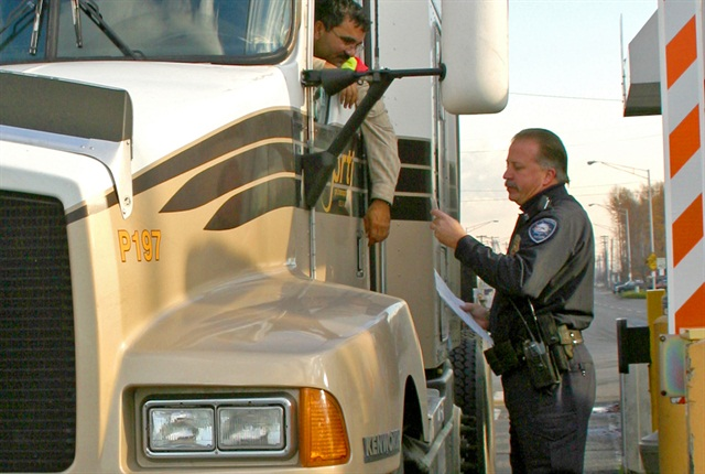 An official manually checks a driver's TWIC credentials at the Port of Tacoma.