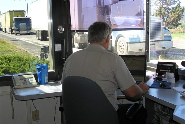 An Oregon DOT motor carrier enforcement officer weighs a truck as a it passes through a Port of Entry.