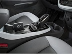 The interior includes a joystick-like shifter and smartphone storage.