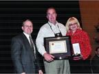 Lynn Weaver of Harrisburg Auto Auction (center) receives the NAAA