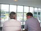 Two fleet managers look out on the Porsche Experience Center's track.